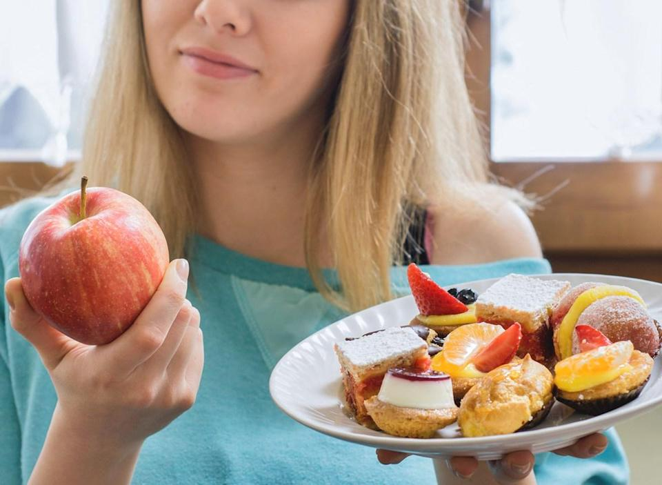 woman choosing healthy apple instead of junk dessert as a food swap to cut calories