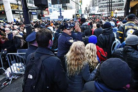 A New York Police officer tries to control the massive traffic of fans while they gather en masse at Super Bowl Boulevard zone ahead of Super Bowl XLVIII in New York February 1, 2014. REUTERS/Eduardo Munoz