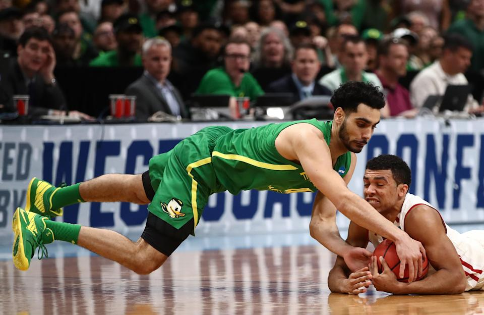 <p>D'Mitrik Trice #0 of the Wisconsin Badgers grabs a loose ball against Ehab Amin #4 of the Oregon Ducks in the first half during the first round of the 2019 NCAA Men's Basketball Tournament at SAP Center on March 22, 2019 in San Jose, California. </p>