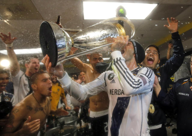 Los Angeles Galaxy's David Beckham, center, of England, drinks champagne from the cup as they celebrate in the dressing room after defeating the Houston Dynamo 3-1 in the MLS Cup championship soccer game, Saturday, Dec. 1, 2012, in Carson, Calif. (AP Photo/Jae C. Hong)