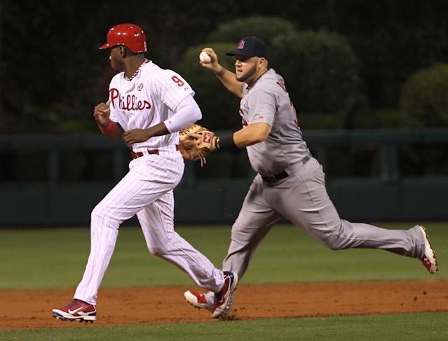 St. Louis Cardinals' Matt Adams runs past Philadelphia Phillies' Domonic Brown on a throwing error to third as Ryan Howard scores on a hit by Carlos Ruiz in the third inning of a baseball game, Friday, Aug. 22, 2014, in Philadelphia. (AP Photo/Laurence Kesterson)