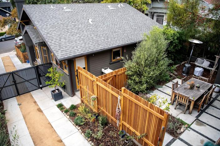 The front house and a patio with a wooden dining table are seen from above
