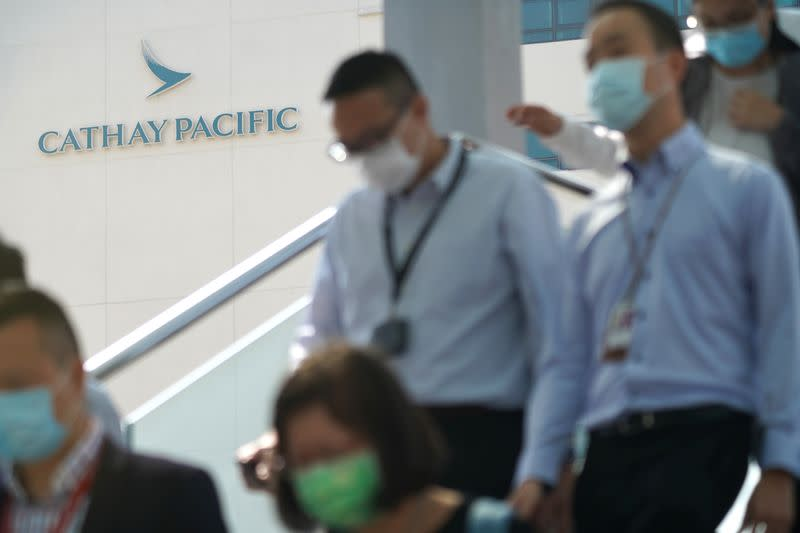 People wearing face masks following the coronavirus disease (COVID-19) outbreak, walk out of Cathay City, the headquarters of Cathay Pacific