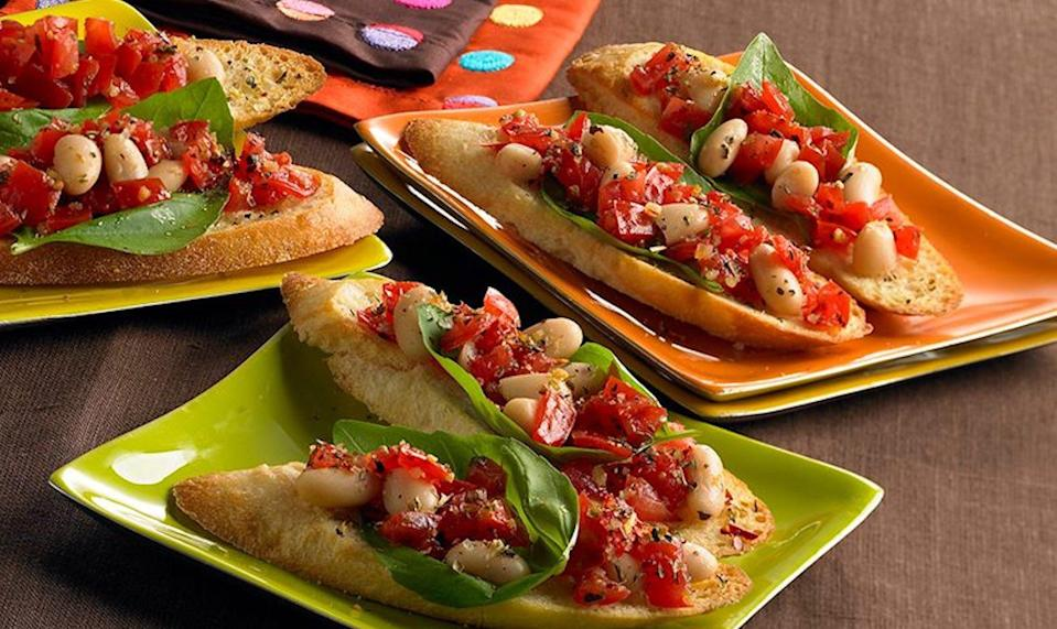 """<p>All it takes is less than 25 minutes to prep and cook these light and impressive appetizers. Ripe tomatoes are good for a <a href=""""https://www.thedailymeal.com/healthy-eating/blood-pressure-lowering-foods-drinks?referrer=yahoo&category=beauty_food&include_utm=1&utm_medium=referral&utm_source=yahoo&utm_campaign=feed"""" rel=""""nofollow noopener"""" target=""""_blank"""" data-ylk=""""slk:blood-pressure conscious diet"""" class=""""link rapid-noclick-resp"""">blood-pressure conscious diet</a> and the coarsely chopped cannellini beans add a signature Mediterranean flare. </p> <p><strong><a href=""""https://www.thedailymeal.com/best-recipes/mediterranean-white-bean-bruschetta?referrer=yahoo&category=beauty_food&include_utm=1&utm_medium=referral&utm_source=yahoo&utm_campaign=feed"""" rel=""""nofollow noopener"""" target=""""_blank"""" data-ylk=""""slk:For the Mediterranean White Bean Bruschetta recipe, click here."""" class=""""link rapid-noclick-resp"""">For the Mediterranean White Bean Bruschetta recipe, click here.</a></strong></p>"""