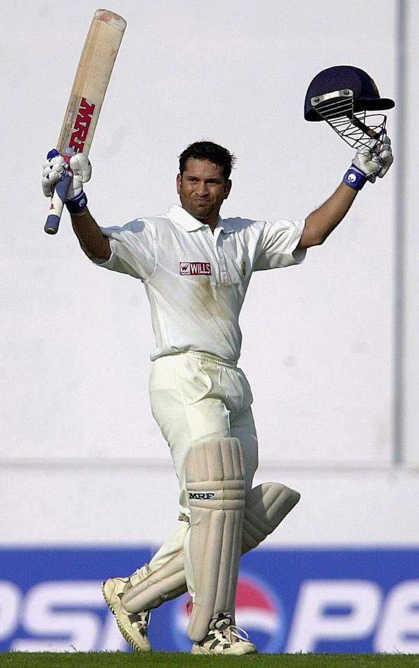 Indian ace batsman Sachin Tendulkar raises his bat and helmet to acknowledge the cheering crowd after scoring a double century on the second day of the second Test match between India and Zimbabwe, 26 November 2000 in Nagpur. Sachin Tenulkar remained unbeaten on 201 as India declared at 609 runs for six wickets.  AFP PHOTO/ARKO DATTA