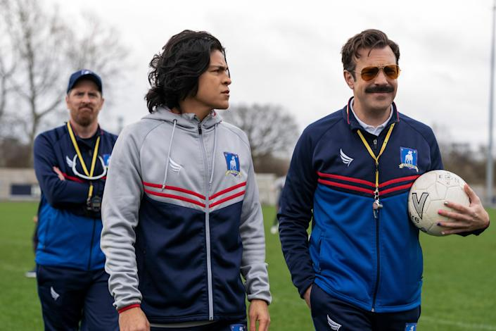 """Brendan Hunt as Coach Beard, Cristo Fernández as Danny Rojas and Jason Sudeikis as Ted in """"Ted Lasso"""" Season 2."""