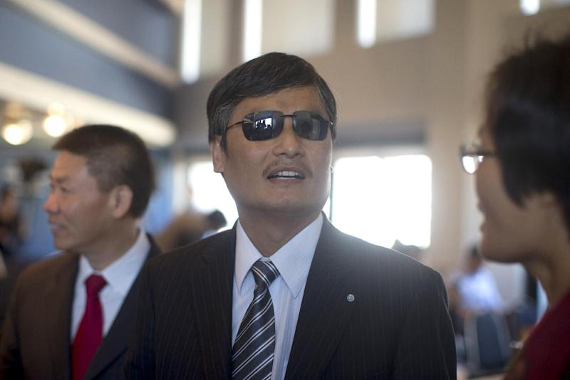 Chinese activist Chen Guangcheng talks with Weighing Yuan, right, before speaking at the National Press Club in Washington, Wednesday, Oct. 2, 2013. Guangcheng says he has new affiliations with three U.S. institutions after leaving New York University under disputed circumstances. (AP Photo/Carolyn Kaster)