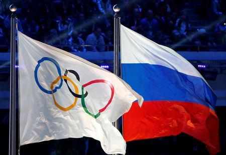 FILE PHOTO: The Russian national flag (R) and the Olympic flag are seen during the closing ceremony for the 2014 Sochi Winter Olympics, Russia, February 23, 2014. REUTERS/Jim Young/File Photo