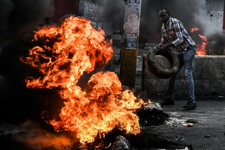 (FILES) In this file photo taken on September 20, 2019 a man uses burning tires to cut off a street to protest against fuel shortages and to demand the resignation of President Jovenel Moise, in Port-au-Prince, Haiti. The UN has called for calm 8t days before the end of its police mission (AFP Photo/CHANDAN KHANNA)