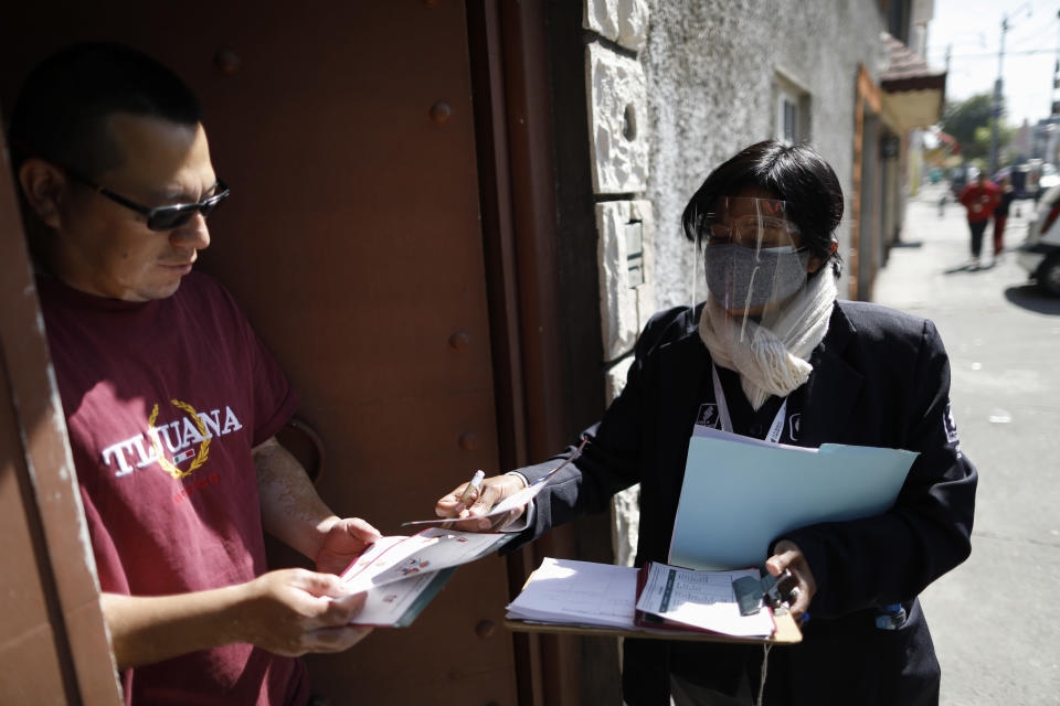 Social worker Guadalupe Ramos, right, of the Romero Rubio Health Center, gives informational materials about good nutrition to improve the immune system and hygiene measures to prevent coronavirus transmission to the husband of a woman who is in isolation inside their home, as Ramos makes house calls to follow up with people who have tested positive for COVID-19, in Mexico City, Wednesday, Oct. 7, 2020. (AP Photo/Rebecca Blackwell)