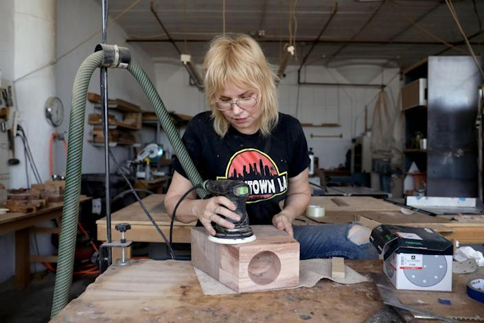 A woman in a woodworking studio uses a mechanical sander on a wooden box