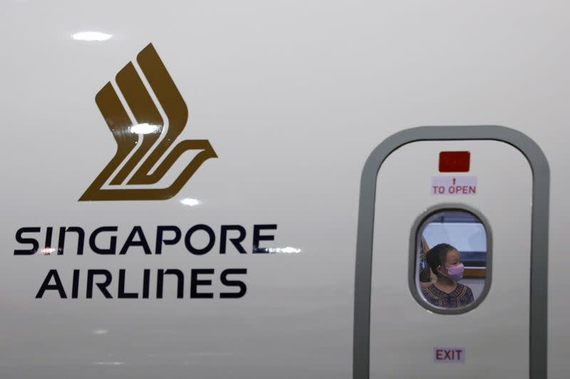 FILE PHOTO: A girl wearing a Singapore Airlines cabin crew uniform is pictured through a window of a replica aircraft during a guided tour at the Singapore Airlines Training Centre in Singapore