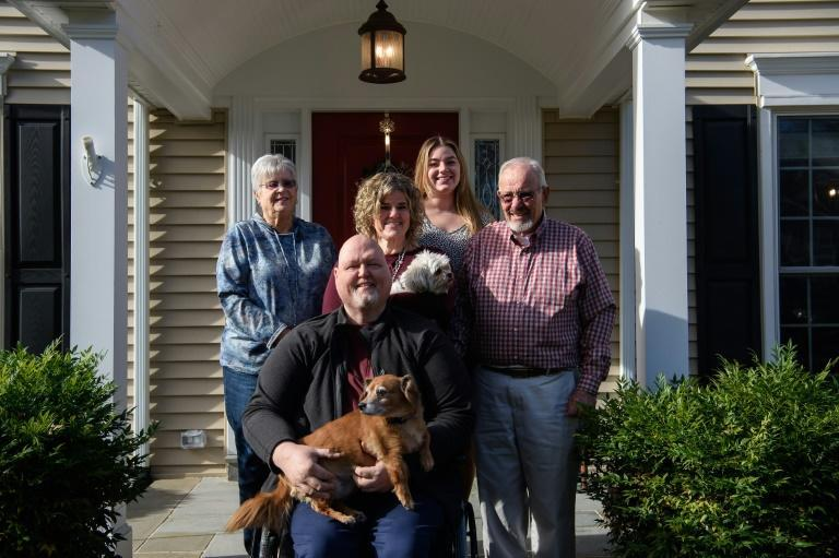 Eric Marcoux (C) poses with his wife Katie (2nd row C), her mother Judy Christensen (L), her father Dano Christensen (R) and daughter Eva Kolb in front of their house in Potomac, Maryland, on December 3, 2020