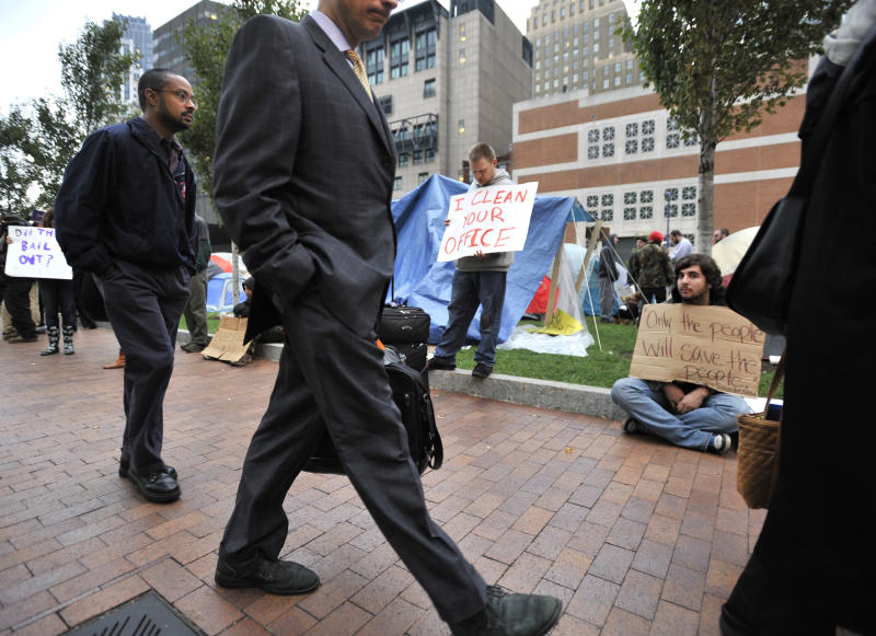 Commuters walk past demonstrators with Occupy Boston outside their tent village in Boston's Financial district,  Monday, Oct. 3, 2011. The group is part of a nationwide grassroots movement in support of the ongoing Wall Street protests in New York. (AP Photo/Josh Reynolds)