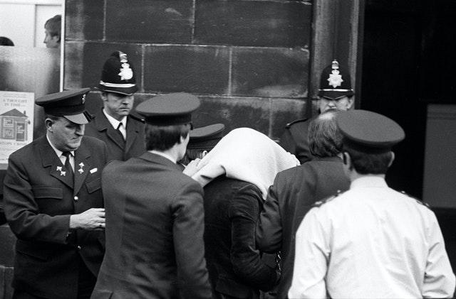 Peter Sutcliffe, under a blanket, arriving at Dewsbury Magistrates Court (PA)