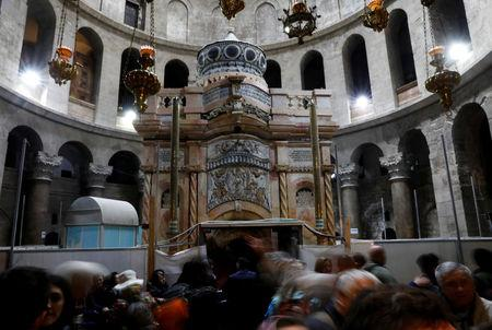 Visitors stand near the newly restored Edicule, seen at the completion of months of restoration works, at the Church of the Holy Sepulchre in Jerusalem's Old City