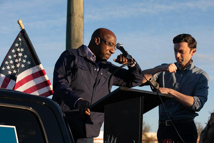Georgia Democratic U.S. Senate candidates Jon Ossoff (R) and Raphael Warnock (L) taps elbows during a rally for supporters on November 15, 2020 in Marietta, Georgia. (Photo by Jessica McGowan/Getty Images)