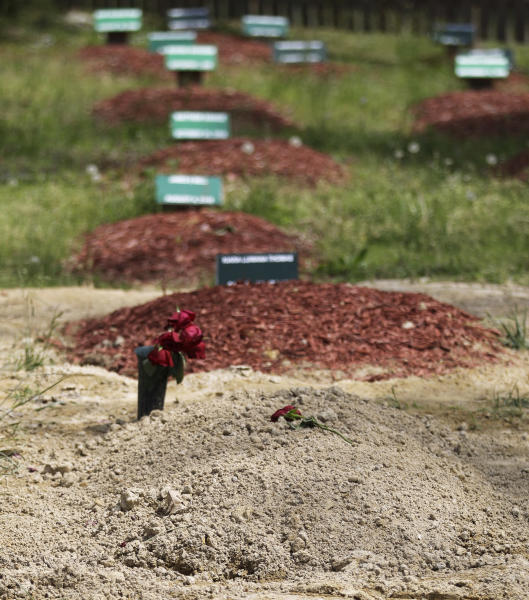 ADDS THAT TSARNAEV'S GRAVE IS ONE OF TWO NEWLY DUG GRAVES AT THE CEMETERY - Flowers are placed on one of two newly dug graves at the Doswell, Va. cemetery where Boston Marathon bombing suspect Tamerlan Tsarnaev is buried, Friday, May 10, 2013. Ruslan Tsarni, the uncle of Tamerlan Tsarnaev, said his nephew was buried in the cemetery north of Richmond. Tsarnaev was killed April 19 in a getaway attempt after a gun battle with police. His younger brother, Dzhokhar, was captured later and remains in custody. It is unknown which grave contains Tsarnaev's remains. (AP Photo/Luis Alvarez)