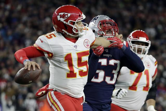 Kansas City Chiefs quarterback Patrick Mahomes grabs the face mask of New England Patriots linebacker Kyle Van Noy, right, as he rolls out to pass in the second half of an NFL football game, Sunday, Dec. 8, 2019, in Foxborough, Mass. Mahomes was penalized on the play. (AP Photo/Elise Amendola)