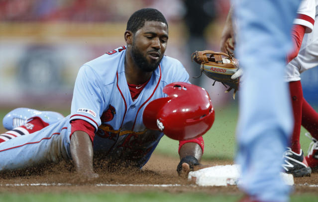 St. Louis Cardinals' Dexter Fowler is tagged out at third base by Cincinnati Reds' Jose Peraza trying to advance on a single by Marcell Ozuna during the fifth inning of a baseball game Saturday, Aug. 17, 2019, in Cincinnati. (AP Photo/Gary Landers)