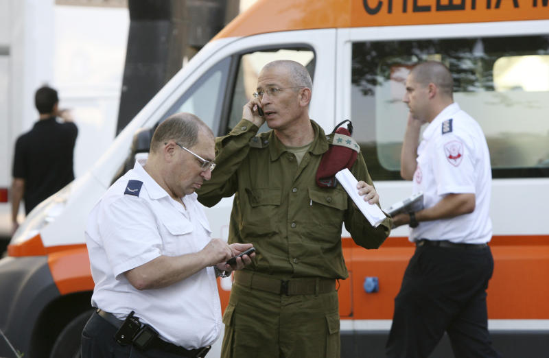 Israeli military and medical personnel talk in front of a hospital in the city of Burgas, Bulgaria, Thursday, July 19, 2012. A daytime bombing that killed eight people and injured dozens on a bus full of Israeli tourists was most likely a suicide attack, Bulgaria's interior minister said Thursday. He said the suspected attacker was carrying a Michigan driver's license that was being sent to the FBI for authentication. (AP Photo/Impact Press Group)