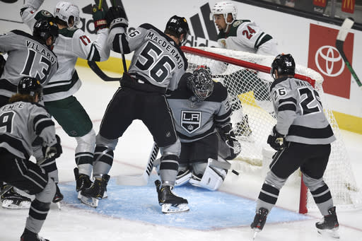 Los Angeles Kings goalie Jonathan Quick, center, looks down after allowing a goal by Minnesota Wild defenseman Mathew Dumba, back, during the first period of an NHL hockey game in Los Angeles, Saturday, Jan. 16, 2021. (AP Photo/Kelvin Kuo)