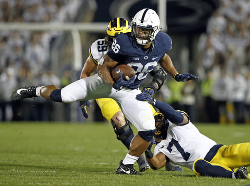 Penn State's Saquon Barkley (26) makes a move on Michigan's Khaleke Hudson (7) during the first half of an NCAA college football game in State College, Pa., Saturday, Oct. 21, 2017. (AP Photo/Chris Knight)