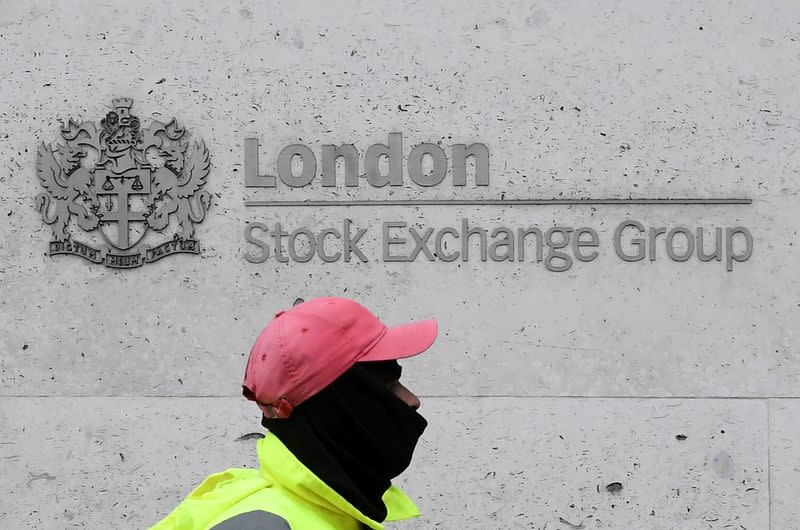 FILE PHOTO: A street cleaning operative walks past the London Stock Exchange Group building in the City of London financial district, whilst British stocks tumble as investors fear that the coronavirus outbreak could stall the global economy, in London