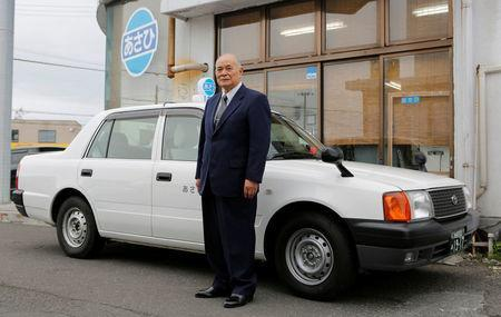 Tadashi Sato, 81, head of the general affairs division of the taxi company Asahi Taxi, poses for a photograph in front of the company office in Akita, Akita prefecture, northern Japan June 20, 2018. Picture taken June 20, 2018. REUTERS/Kiyoshi Takenaka