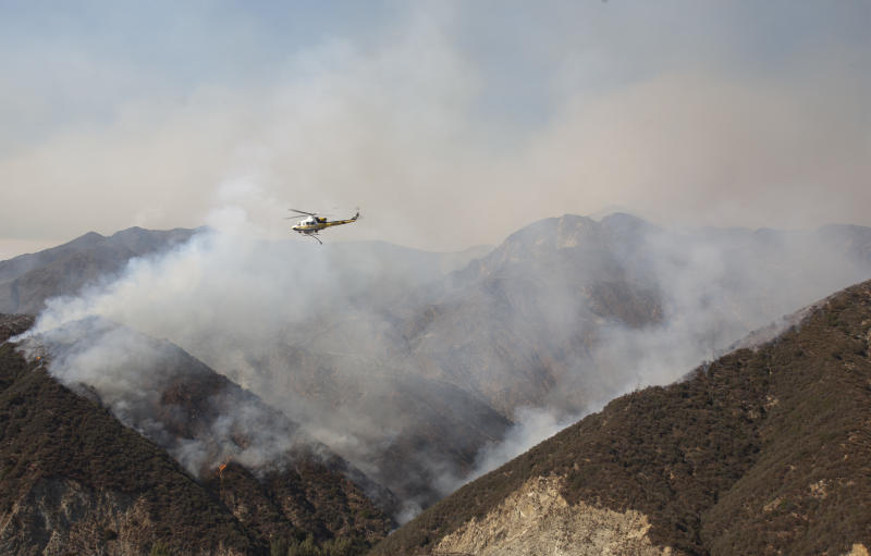 A firefighting helicopter goes to refill after dropping water on a wildfire in the Angeles National Forest north of Glendora, Calif. Monday, Sept. 3, 2012. A day after the wildfire broke out near a campground and forced the evacuation of thousands of campers and picnickers it had grown to more than 4,100 acres, or roughly 6 square miles, and was just five percent contained. (AP Photo/Jason Redmond)