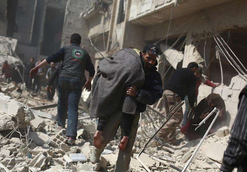 A man carries a wounded person in the rebel-held area of Douma, east of the Syrian capital Damascus, following reported air strikes by regime forces on March 15, 2015
