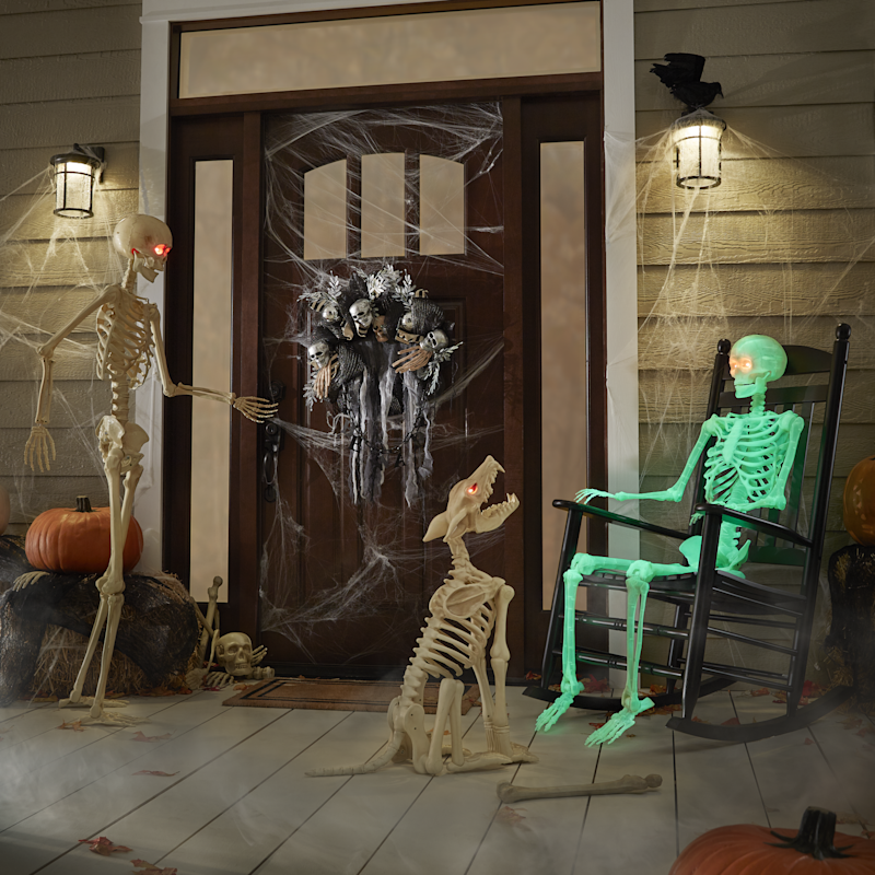 Dark front porch with a green skeleton in a rocking chair next to a plastic wolf skeleton