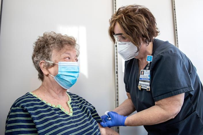 Eleanor Leisenring speaks with Cheryl McHale, RN, after receiving the COVID-19 vaccine at a Geisinger community vaccine center in Danville, Pa.