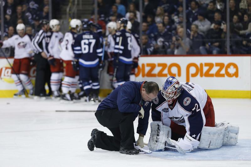 Columbus Blue Jackets goaltender Sergei Bobrovsky (72) is treated on the ice after an injury during the second period of an NHL hockey game against the Winnipeg Jets on Wednesday, Jan. 21, 2015, in Winnipeg, Manitoba