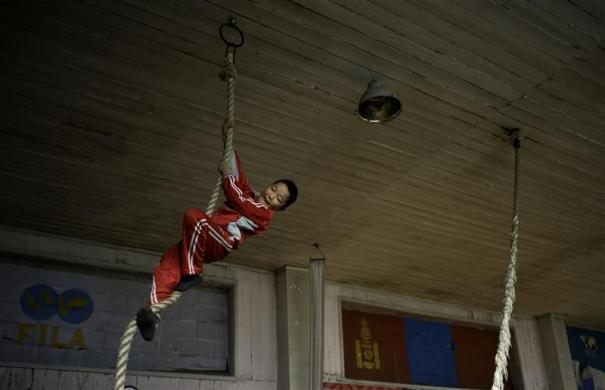 A child climbs a rope in the same gym as Mongolia's Olympic freestyle 60kg wrestler Mandakhnaran Ganzorig in Ulan Batur October 27, 2011.