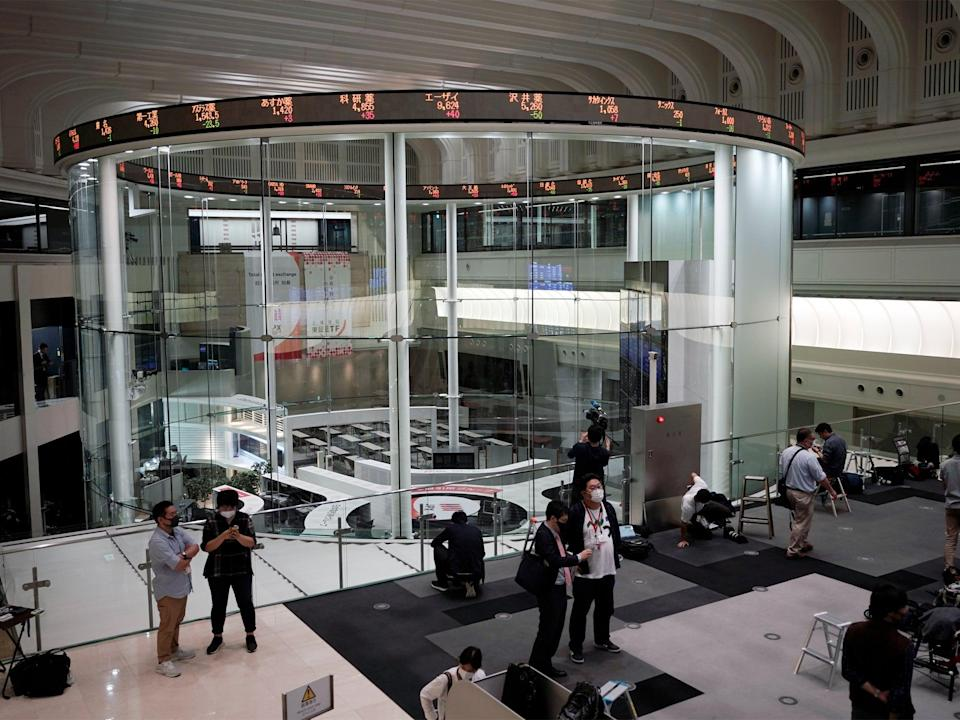 Journalists film an electronic stock board showing reopened Japan's Nikkei 225 index at Tokyo Stock Exchange in Tokyo Friday, Oct. 2, 2020. Tokyo's market resumed trading Friday after a full-day outage due to a malfunction in its computer systems (Associated Press)