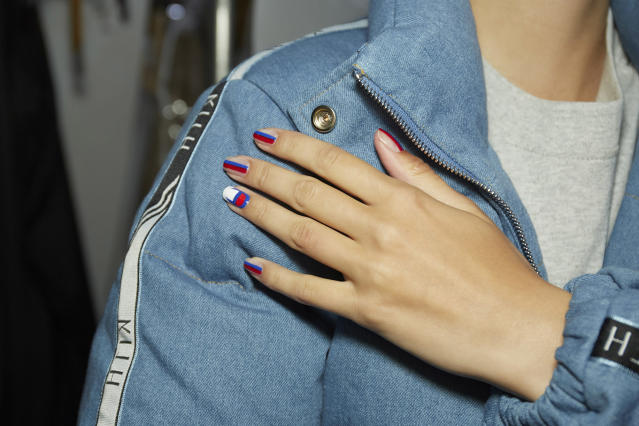 <p>Nail artist Alice Torello for Essie designed a mani that fused racing stripes with the Champion logo with Really Red, Blanc, and Butler Please polishes. (Photo: Essie) </p>