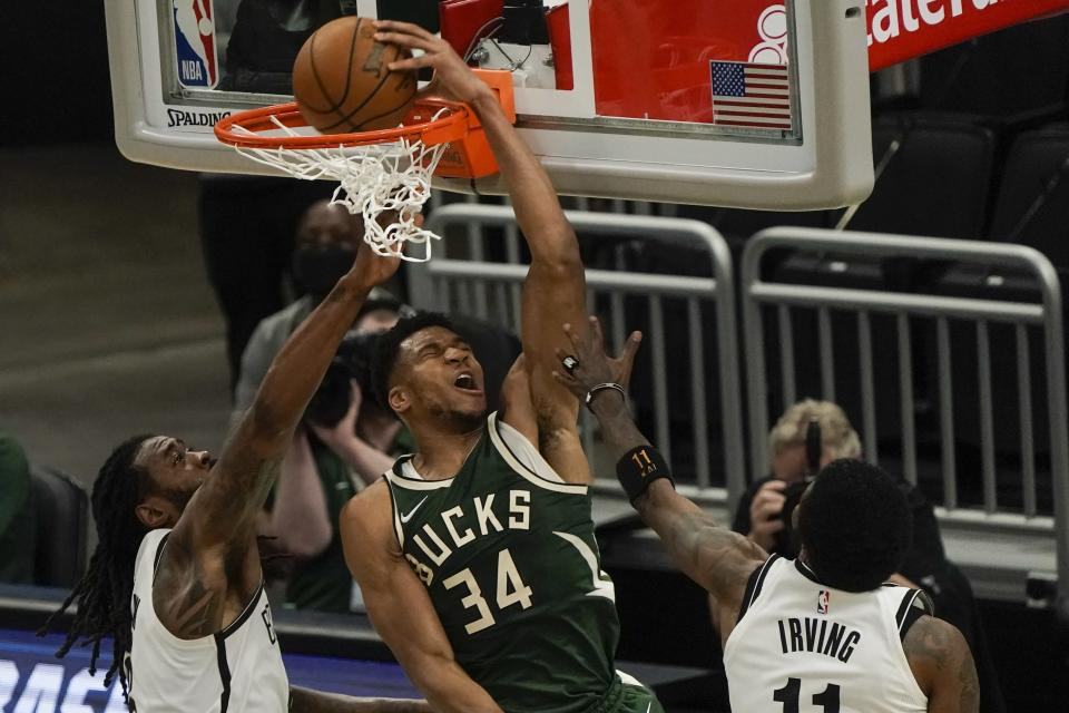 Milwaukee Bucks' Giannis Antetokounmpo dunks in front of Brooklyn Nets' DeAndre Jordan during the first half of an NBA basketball game Sunday, May 2, 2021, in Milwaukee. (AP Photo/Morry Gash)