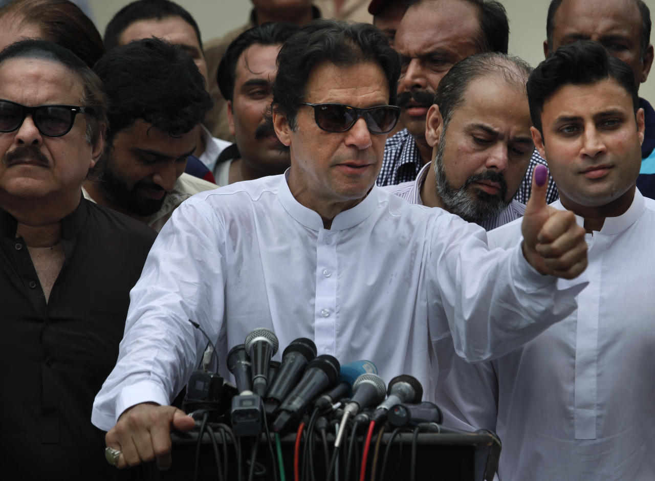 FILE - In this Wednesday, July 25, 2018 file photo. Pakistani politician Imran Khan, chief of Pakistan Tehreek-e-Insaf party, shows his marked thumb after casting his vote at a polling station for the parliamentary elections in Islamabad, Pakistan. Pakistani lawmakers on Friday elected former cricket star and longtime politician Khan as the country's next prime minister in a step toward third straight transfer of power from one civilian government to another one.(AP Photo/Anjum Naveed,file)