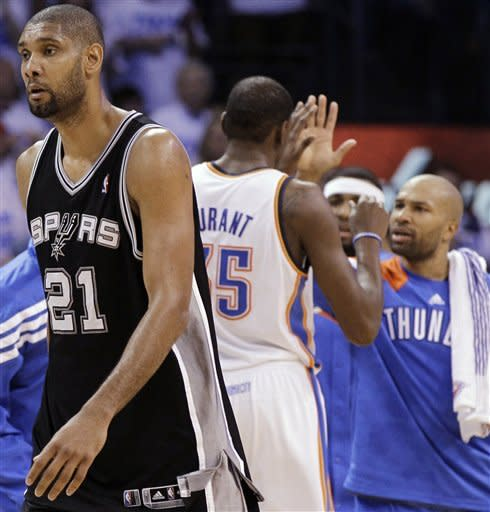 San Antonio Spurs center Tim Duncan (21) heads to the bench as Oklahoma City Thunder forward Kevin Durant (35) and Derek Fisher celebrate during the first half of Game 4 in the NBA basketball playoffs Western Conference finals, Saturday, June 2, 2012, in Oklahoma City. (AP Photo/Eric Gay)