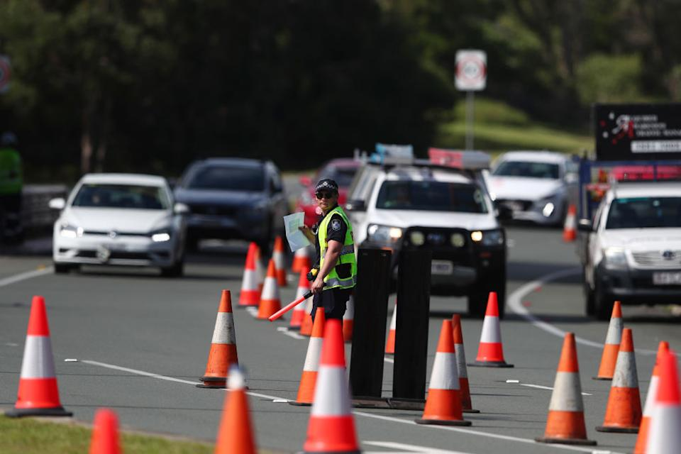Queensland Police stop vehicles at a Police checkpoint set up at the Queensland and New South Wales border in Coolangatta on the Gold Coast, Australia.