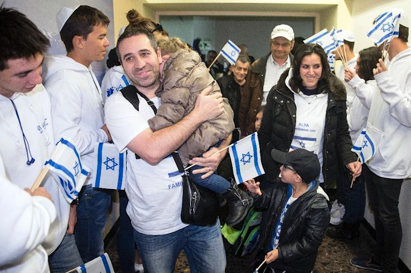 Jewish new immigrants from France are welcomed by Israelis upon their arrival at Ben Gurion International Airport on December 8, 2015