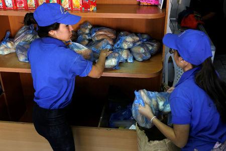 Saleswomen grab bags of bread at a bakery in Caracas, Venezuela March 17, 2017. REUTERS/Marco Bello