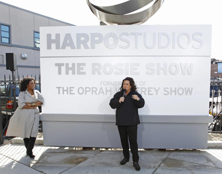 "FILE-This Sept. 15, 2011, file photo shows Rosie O'Donnell, right, with Oprah Winfrey looking on, speaking to the media after the unveiling of a new sign outside Harpo Studios welcoming ""The Rosie Show,"" to the studio in Chicago. Winfrey is selling Harpo Studios in Chicago to a developer, but the studio will remain on the property for another two years. Harpo Inc. said in a statement that it has entered into a purchasing agreement with Sterling Bay Cos. for the four-building campus on Chicago's West Side. (AP Photo/M. Spencer Green, File)"