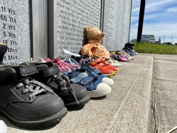 A monument in Fort Providence, N.W.T., memorializes around 300 people buried in unmarked graves, including 161 children who were brought to a residential school in the community from up and down the Mackenzie River Valley. (Kate Kyle/CBC - image credit)