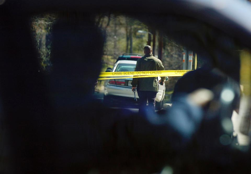 Motorists slow down to watch law enforcement officers at a crime scene at the corner of Canter Road and Lennox Road in Atlanta on Saturday, March 12. (Photo by Davis Turner/Getty Images)