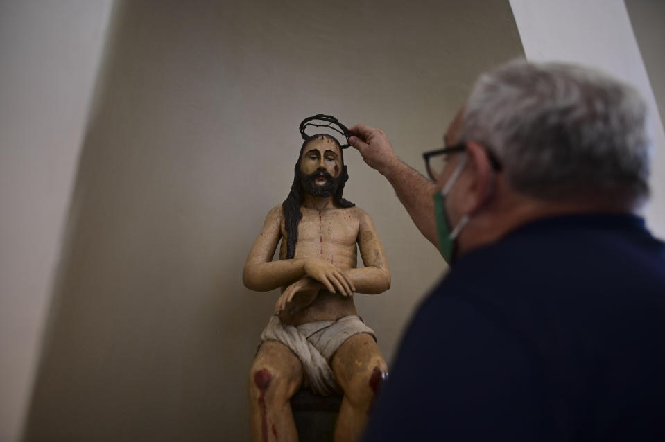 Architect Jorge Rigau arranges a crown of thorns on a statue of Jesus inside the San Jose Church, the second oldest Spanish church in the Americas, that will reopen following a massive reconstruction that took nearly two decades to complete, in San Juan, Puerto Rico, Tuesday, March 9, 2021. The church's construction began by 1532 on land donated by famous explorer Juan Ponce de León and whose base was erected atop an Indigenous settlement. (AP Photo/Carlos Giusti)