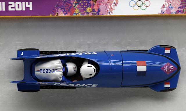 The team from France FRA-1, piloted by Loic Costerg and brakeman Romain Heinrich, take a turn during the men's two-man bobsled competition at the 2014 Winter Olympics, Sunday, Feb. 16, 2014, in Krasnaya Polyana, Russia. (AP Photo/Michael Sohn)
