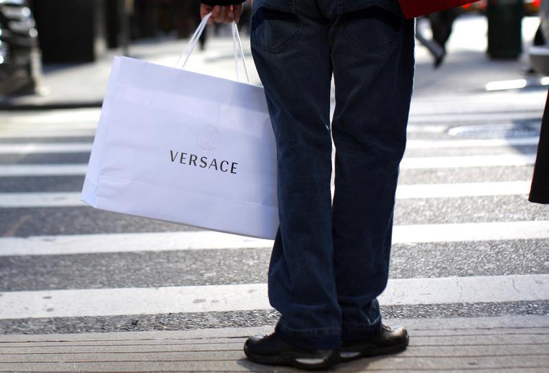 Shopper holds Versace bag on 5th Avenue in New York as holiday shopping season begins