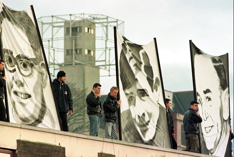 File - Protestors hold banners showing portraits of three of the thirteen killed on Bloody Sunday, against a backdrop of a security tower in this Sunday, Feb. 1, 1998 file photo, in Londonderry, Northern Ireland. The rally was held to honor the Irish demonstrators killed during a civil rights march in 1972. Chief Constable Matt Baggott told Northern Ireland's policing board Thursday July 5 2012 that his force is planning a Bloody Sunday investigation that would require 30 detectives and take four years. Northern Ireland's police commander says his detectives will eventually investigate the Bloody Sunday massacre to determine whether any British soldiers should be charged with murder _ but not yet. Families of the 13 people killed when troops opened fire on Irish Catholic demonstrators in 1972 have waited for a criminal investigation to start since 2010, when the biggest fact-finding probe in British history determined that the soldiers targeted unarmed civilians. (AP Photo/Paul McErlane, File)